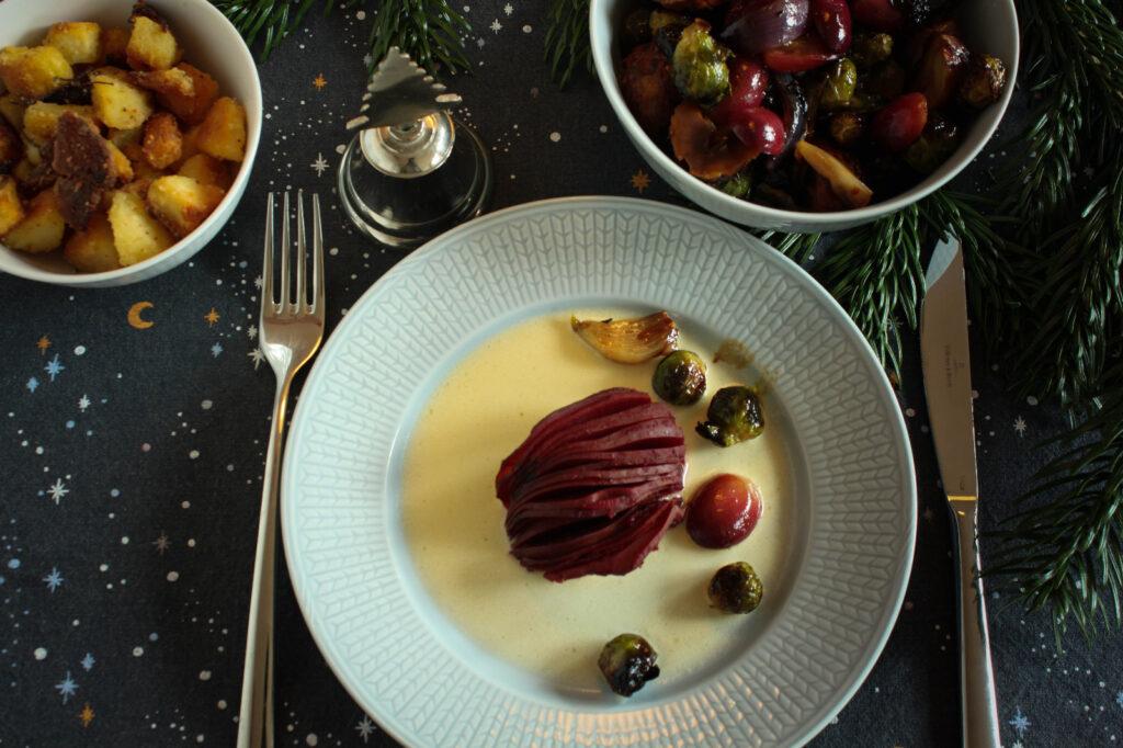 Vegetarisch kerstdiner. Hoofdgerecht mille-feuille van rode biet met spruiten, kastanjes, druiven, aardappels en gekonfijte knoflook